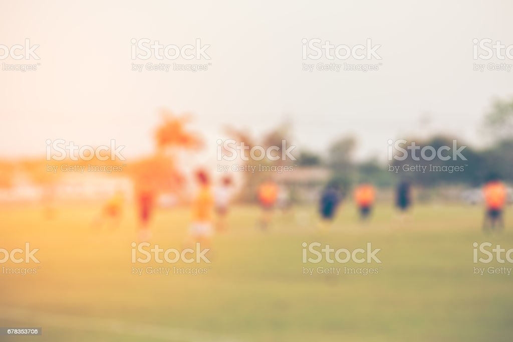 Shallow depth of field shot of young boys playing a kids soccer match on green turf stock photo