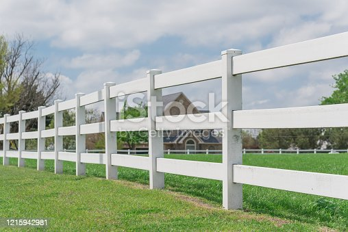 Selective focus on the white fence with blurry two story farm house in background. Long wooden fence along green grass garden under cloud blue sky, farmland ranch in Ennis, Texas, America.