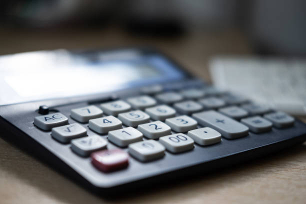 Shallow focus of some of the keys on a typical business orientated digital calculator. Seen on a wooden desk, used for calculating loan repayments. debt ceiling stock pictures, royalty-free photos & images