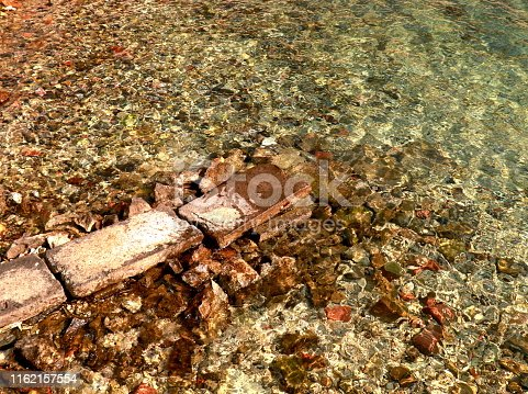 959508862 istock photo Shallow transparent green sea water rocks at the bottom 1162157554