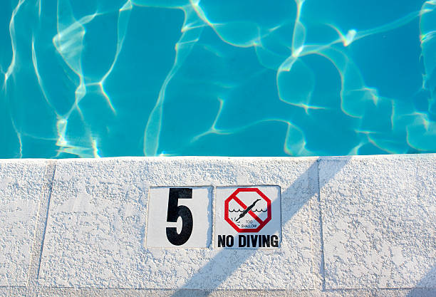 Shallow Water In Pool Close-up of a swimming pool with a no-diving warning. shallow stock pictures, royalty-free photos & images