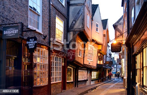 Shambles is probably the most famous street in York. Shambles has been a Shopping street since Tudor times and remains almost unchanged to this day and attracts tourists in the thousands.There are  people in the scene but none of them are recognisable due to a slow shutter speed. Although the sky is white it was almost the last light of the day. The street was very dark and the lights were coming on.