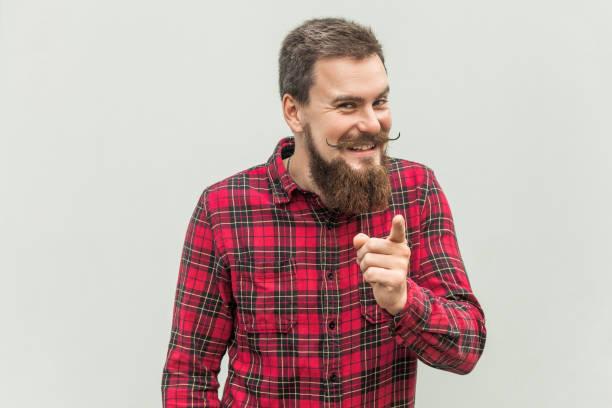 ¡vergüenza de ti! hombre con barba en dedo acusador de camisa roja en cámara y sonrisa toothy - vergüenza fotografías e imágenes de stock