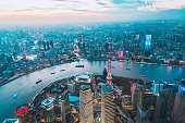 Aerial view of the Shanghai financial district skyscrapers and the Huangpu river at sunset.