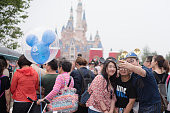 Shanghai, China - June 7, 2016: A group of young chinese people taking a selfie with the Enchanted Castle on the back,  during trial operations before the grand opening of Shanghai Disneyland Park, located in Chuansha New Town of Pudong New Area, which is officially confirmed to open on June 16th, 2016. Is the sixth in the world and the second in China (after Hong Kong Disneyland).