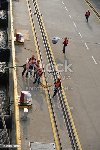 A mooring gang retrieves the hawser and begins to tie down the cruise ship in the Shanghai harbor