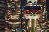The iconic obeservation deck and concrete columns of the Oriental Pearl Tower glowing against the crowded skyscraper cityscape of Pudong, Shanghai's futuristic financial district, China. ProPhoto RGB profile for maximum color fidelity and gamut.