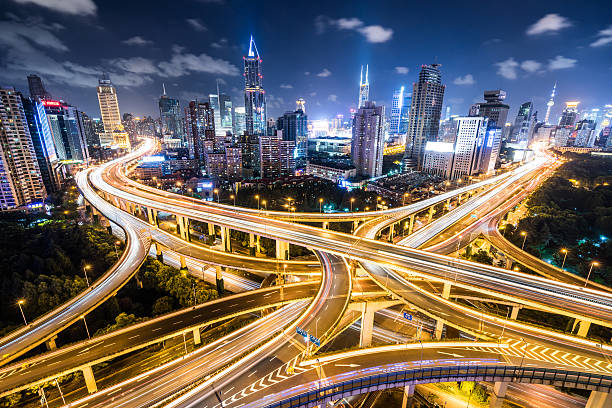 Shanghai Highway at Night Crowds of cars passing a road intersection in downtown Shanghai. overpass road stock pictures, royalty-free photos & images