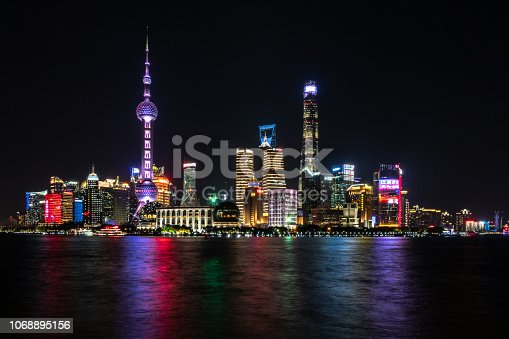Photograph of Shanghai city skyline, Pudong side of river, on Huangpu River at night with beautiful modern skyscrapers and colorful lights