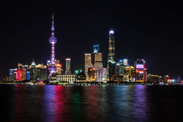 Shanghai Pudong skyline in evening light Photograph of Shanghai city skyline, Pudong side of river, on Huangpu River at night with beautiful modern skyscrapers and colorful lights shanghai stock pictures, royalty-free photos & images