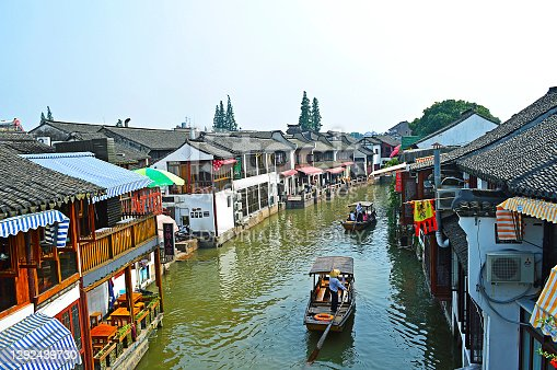Shanghai Zhujiajiao water town, China, July 2015. Two boats with boatmen and tourists pass the houses on the water town canal in a sunny day.