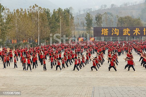Dengfeng, Zhengzhou, Henan, China - October 16, 2018: Shaolin Martial Arts School. A large group of martial arts students are training in the square.