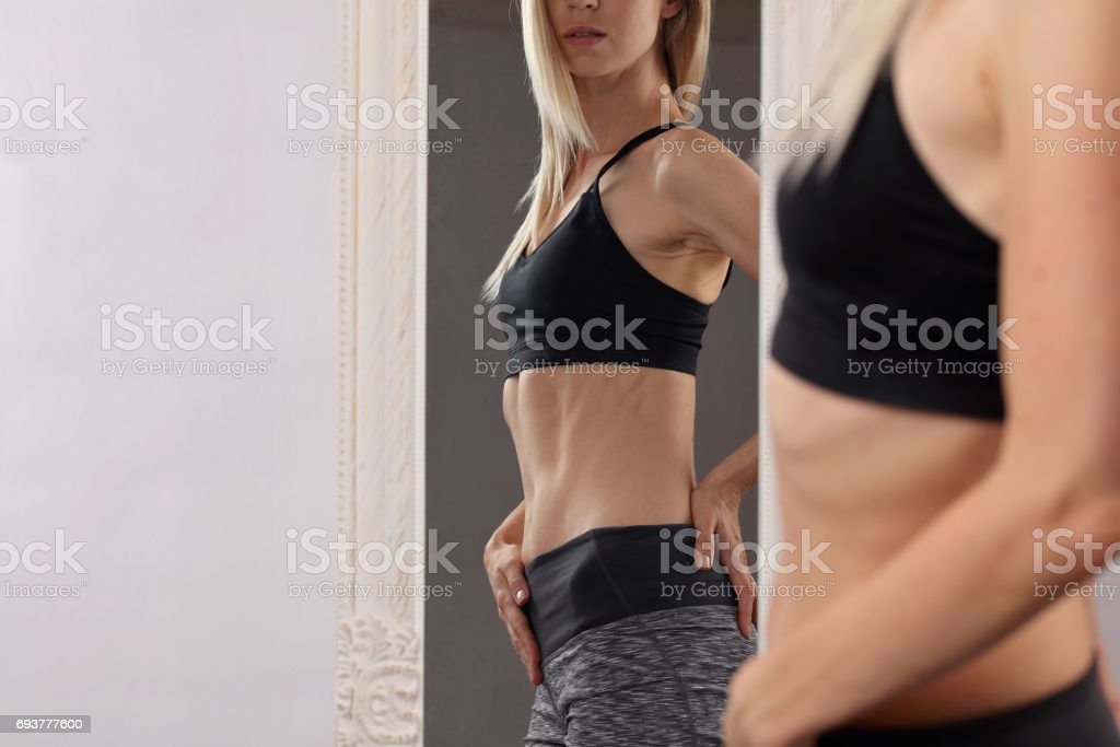 Shape, fit fitness woman in front of Mirror checking Training Results. Female with perfect abdominal muscles and obliques.Healthy nutrition and weight losing concept stock photo