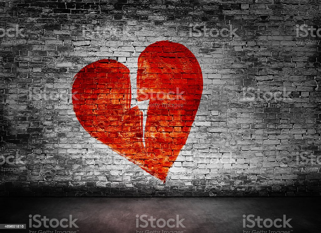 Shape of broken heart on brick wall stock photo