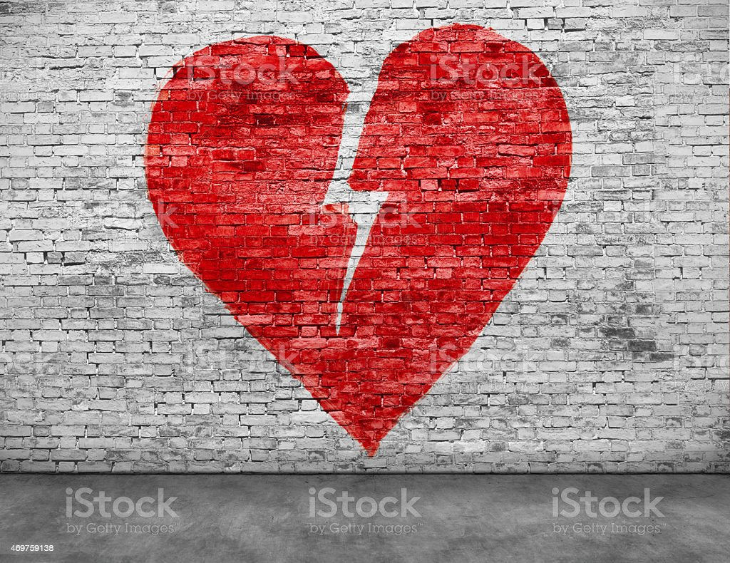 Shape of broken heart painted on brick wall