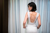 Rear view of a beautiful young woman in a glamourous dress.