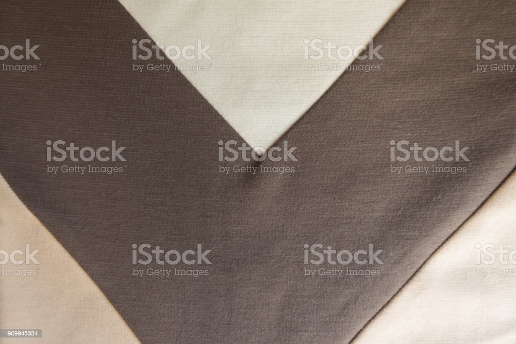 V shaped brown stripe sewn to beige fabric stock photo