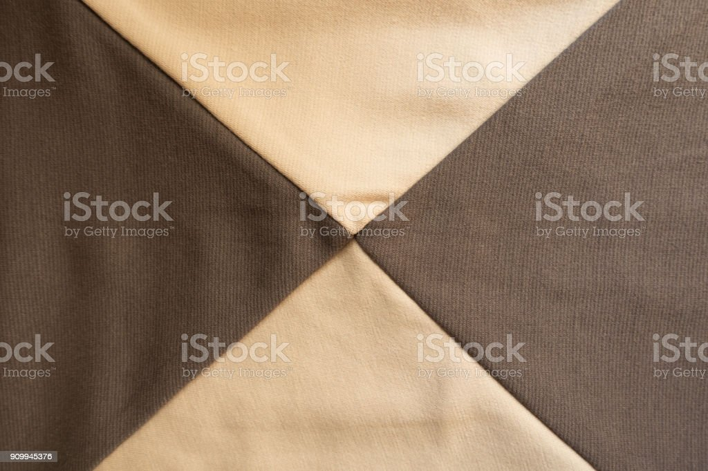 X shaped seams between beige and brown fabrics stock photo