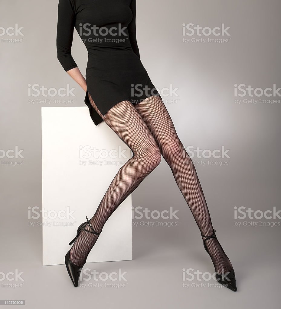 shapely girls  legs with black fishnet tights stock photo