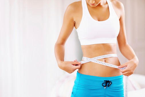 Portrait of young woman measuring her waistline