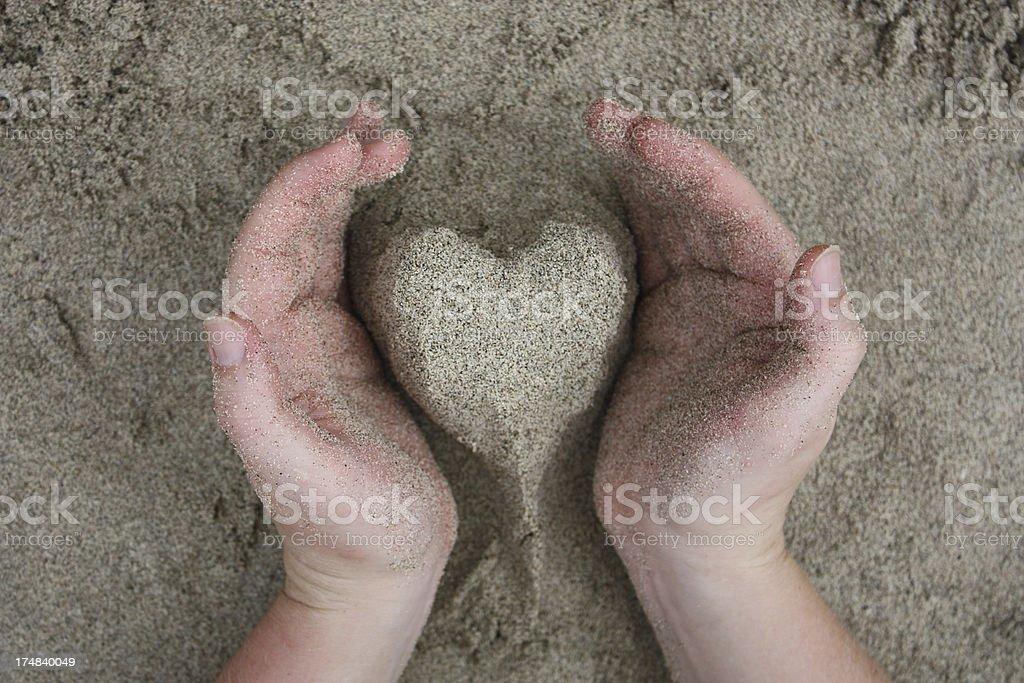 Shaping sand into the shape of a heart. royalty-free stock photo