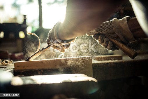 A caucasian senior adult carving wood in a workshop