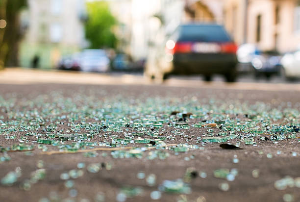 shards of car glass on the street - car accident stock photos and pictures
