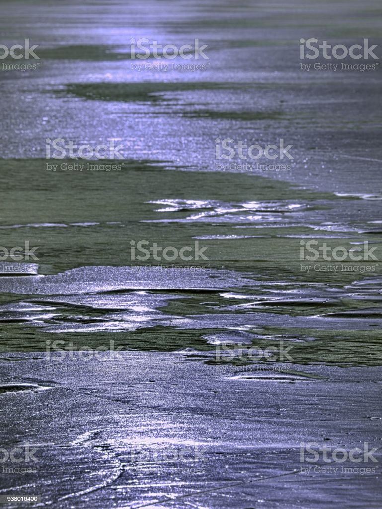 Shards of cracked ice jut out on the frozen lake. The light phenomenon occurs stock photo
