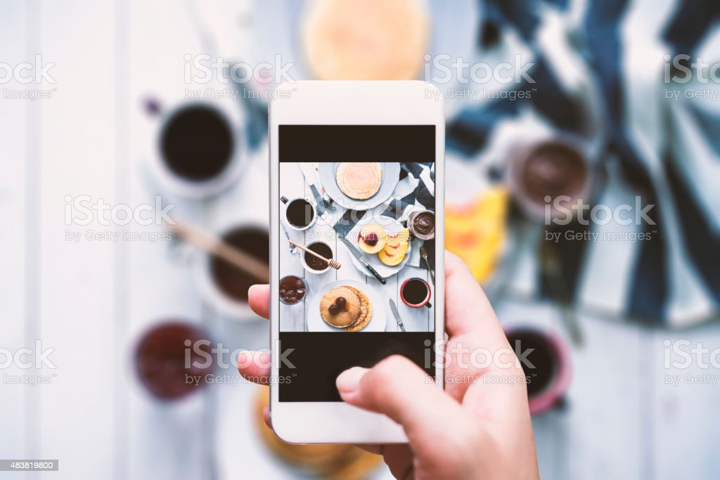 Share the moment Hand taking top view shot of table. Pancakes with strawberry jam for breakfast. Coffee, honey, strawberry jam, chocolate spread and peaches on the table. 2015 Stock Photo