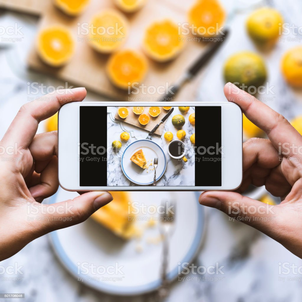 Share the moment Hand taking top view shot of table. Homemade cake, mandarine oranges and cup of coffee are on the table. 2015 Stock Photo