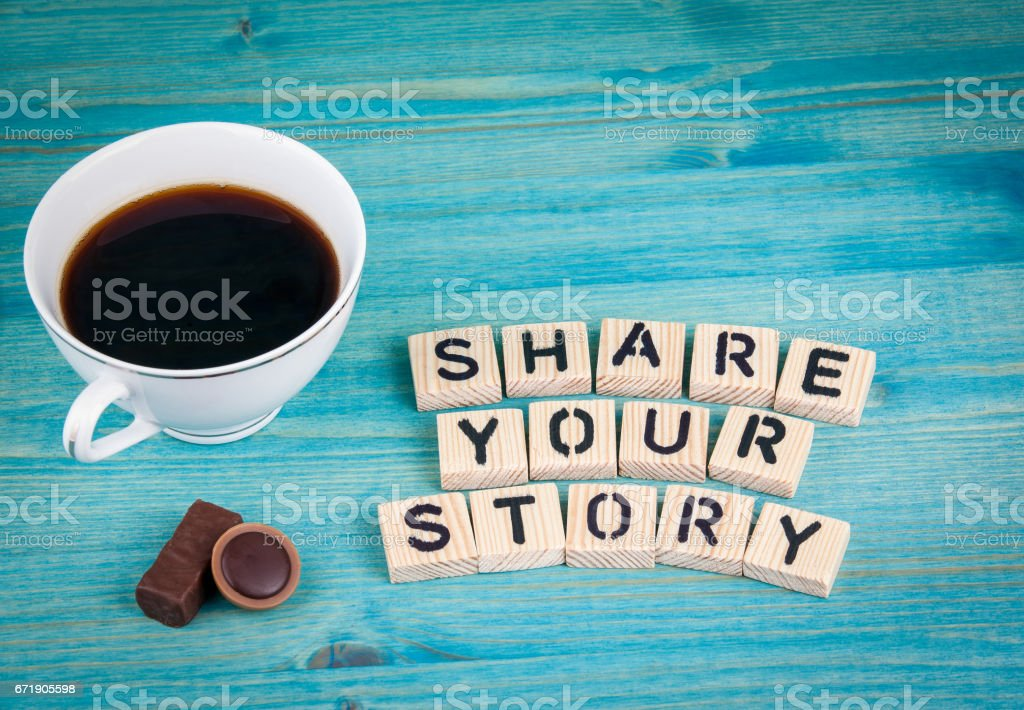 share your story. Coffee mug and wooden letters on wooden background stock photo