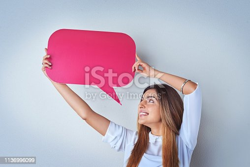 Shot of an attractive young woman holding up a speech bubble against a blue background