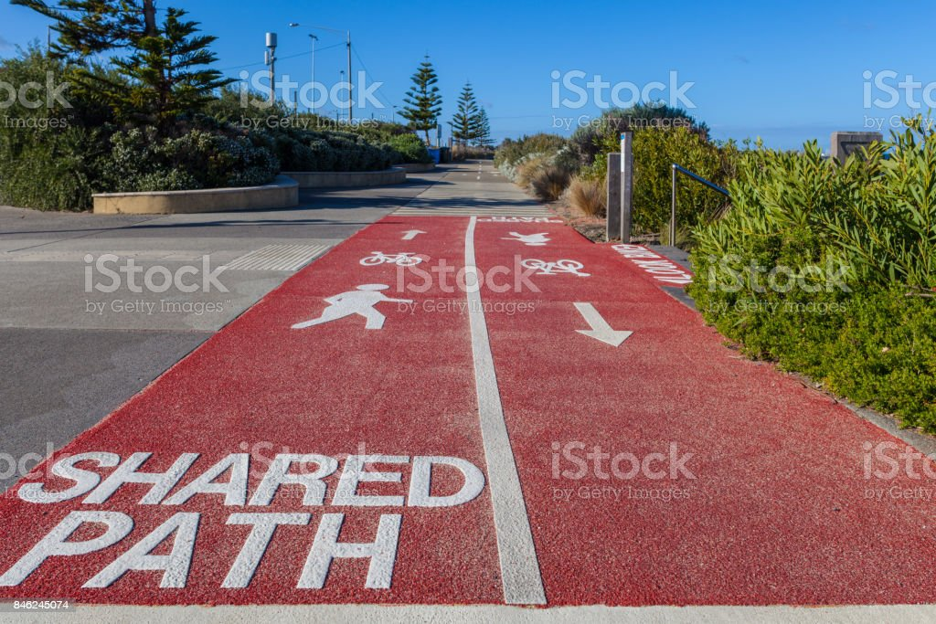 Shared Path sign written on footpath for cyclists and pedestrians with bicycle, walking person, and arrow signs stock photo
