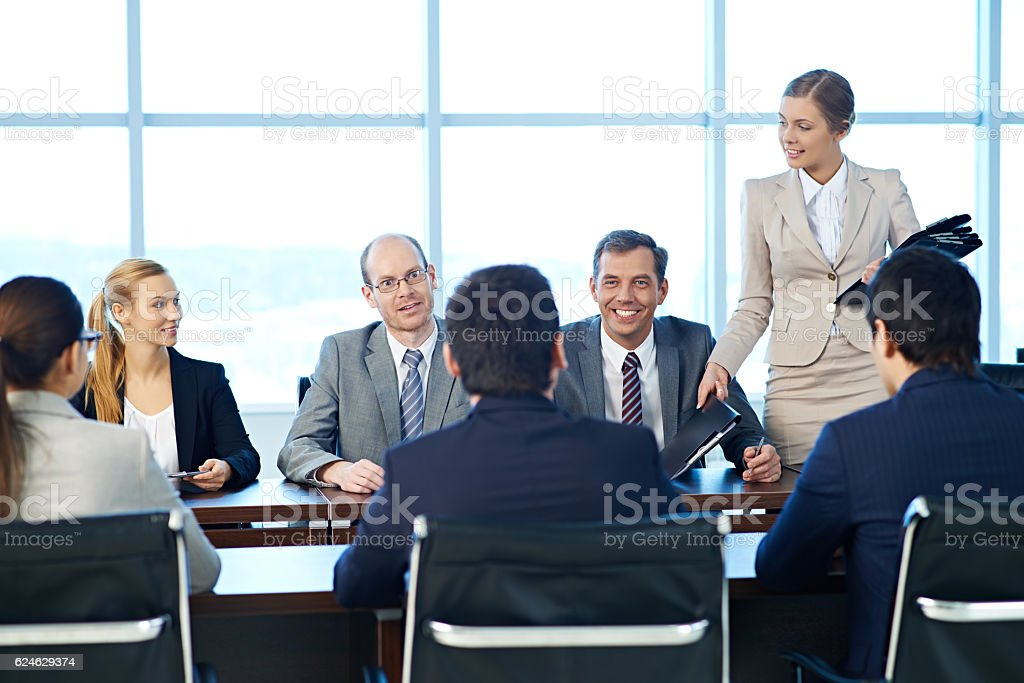 Shareholders having a meeting, a secretary giving out folders with documents stock photo