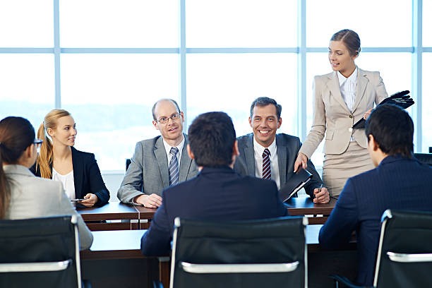 Shareholders having a meeting, a secretary giving out folders with documents - foto stock