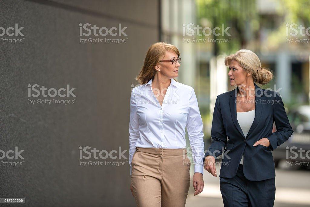 Team of confident businesswomen discussing work outdoors.