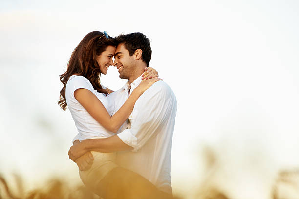 Sharing an intimate moment of romance Loving young couple embracing in a corn field together - copyspace romance stock pictures, royalty-free photos & images