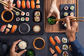 Top view of couple hands eating sushi food at japanese restaurant. High angle view of woman hand serving seaweed in little bowl with sesame to man while holding hosomaki with chopsticks. Couple eating and sharing sushi roll, maki, nigiri, uramaki.