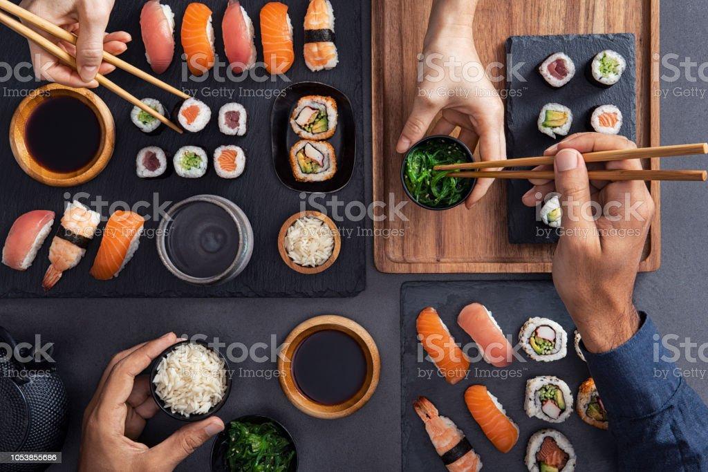 Compartir y comer sushi comida - foto de stock