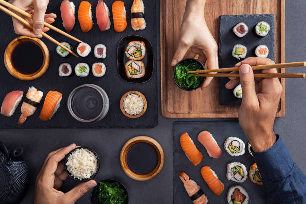 sharing and eating sushi food - japanese food stock photos and pictures