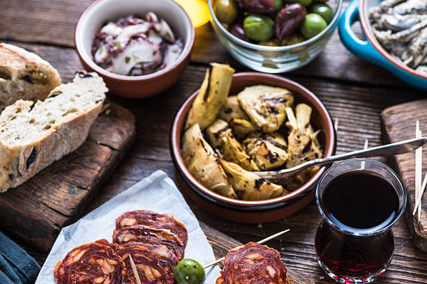 sharing authentic spanish tapas with friends in bar - spanish food stock photos and pictures