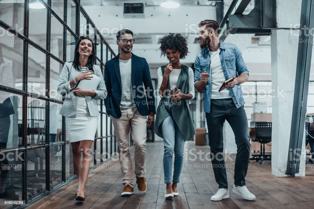 Sharing business experience. Full length of young modern people in smart casual wear having a discussion while walking through the large modern office Adult Stock Photo