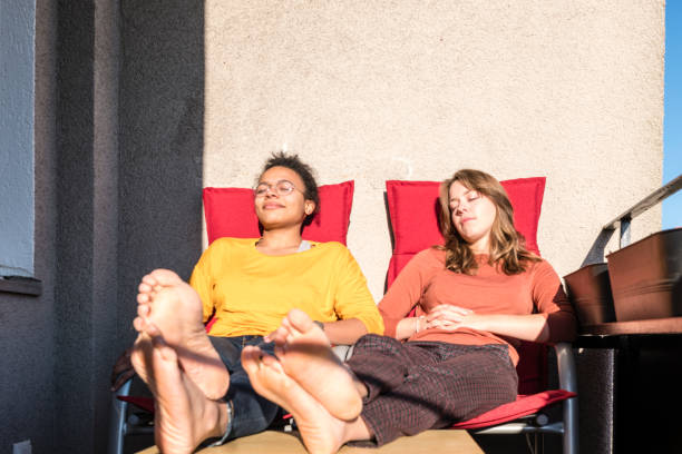 sharing economy: roommates sunbathing together on balcony stock photo