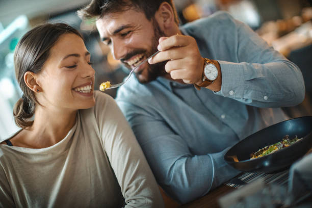 Sharing food during romantic dinner. stock photo