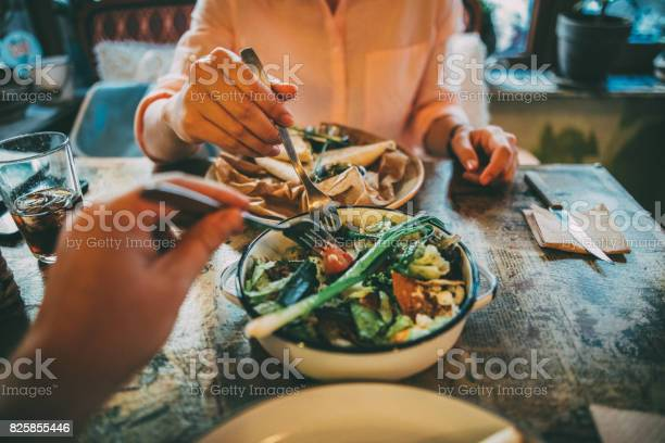 Woman taking some of her boyfriend's salad on lunch at a restaurant.