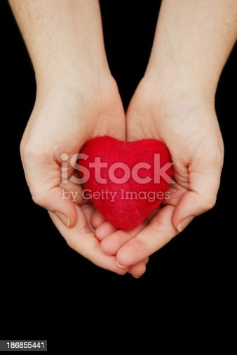 A woman's hands holding out a red felted heart (made by me).  Isolated on black.