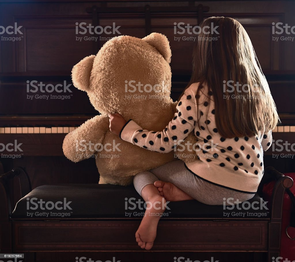 Sharing her talents with her teddy Rear view shot of a little girl sitting in front of a piano with her teddy bear Arts Culture and Entertainment Stock Photo