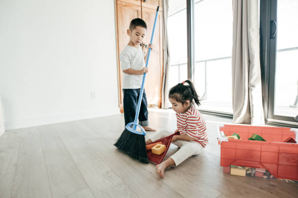 Sharing housework Kids clearing up the mess they made at the room. kids cleaning up toys stock pictures, royalty-free photos & images