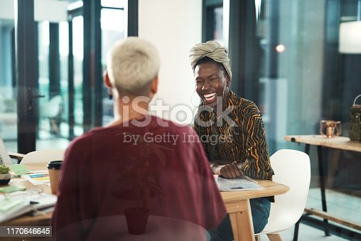 Cropped shot of an attractive young businesswoman sitting and laughing with her female colleague in the office