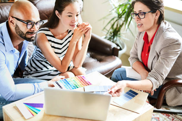 Sharing Ideas with Clients Pretty middle-aged interior designer sharing ideas with her clients while having meeting in cozy boardroom, they listening to her with interest interior designer stock pictures, royalty-free photos & images